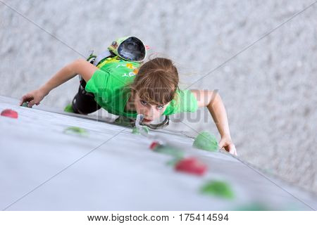 Angel looking girl child Climber moving up on climbing Wall. National Junior climbing Competitions, Dnipro, Ukraine, May 21, 2016