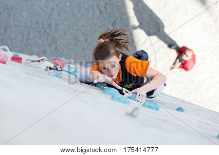 Junior female Athlete makes hard move on climbing Wall of National Competition with very emotional face. Dnipro, Ukraine, May 21, 2016