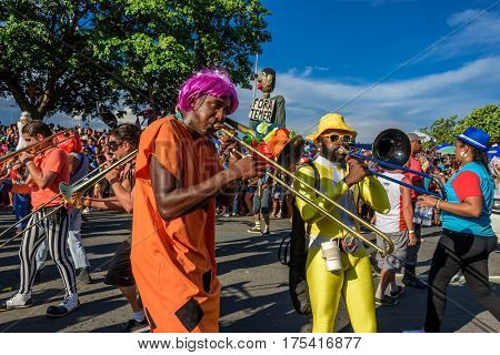RIO DE JANEIRO, BRAZIL - FEBRUARY 28, 2017: Group of costume musicians playing trombones on the background of the doll Fora Temer during Bloco Orquestra Voadora in Flamengo Park, Carnaval 2017