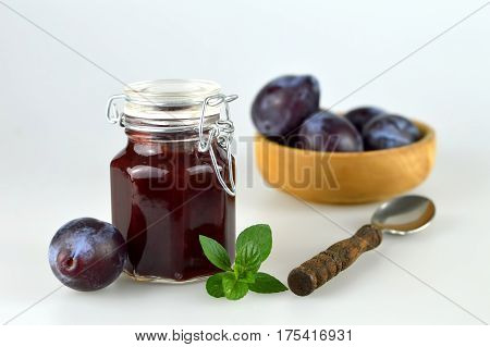 Jar of plum jam and fresh plums