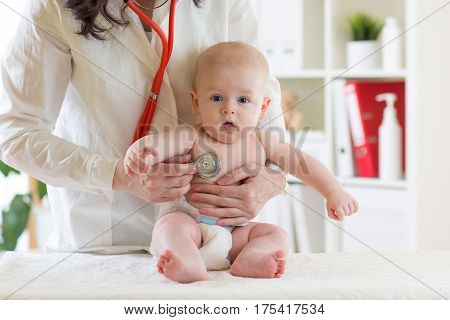 Female pediatrician examining heartbeat of baby boy with stethoscope