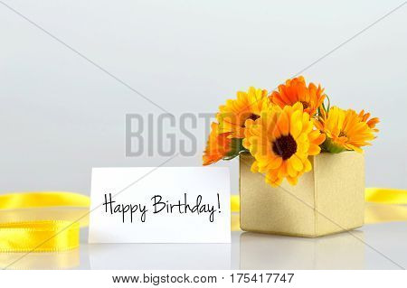 Happy Birthday card and marigold flowers arranged in gift box
