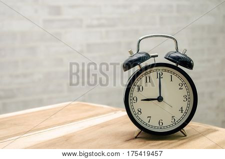 retro vintage clock on wooden table  with wall background, retro vintage concept with copy space for text.