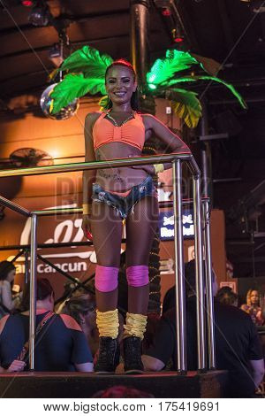 CANCUN MEXICO - MARCH 1 2017: A pretty female go-go dancer stops her dance to pose for the camera at the Congo Bar during Spring break in Cancun.