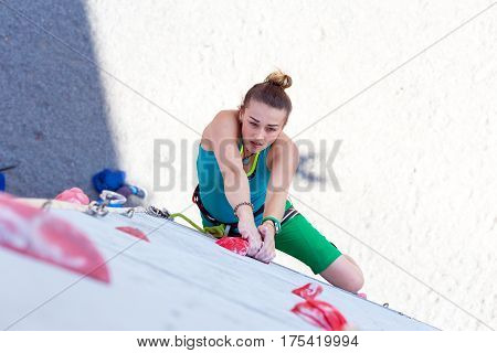 Female climber makes a try on the track of lead climbing competition