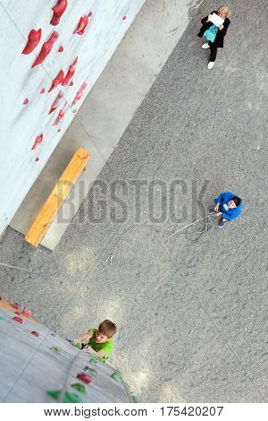 Little Climber boy moving up on climbing Wall his coach belaying him from below while mother making photos on tablet PC. National Junior climbing Competitions, Dnipro, Ukraine, May 21, 2016