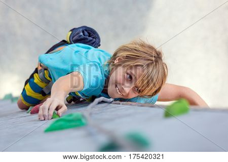 Emotional child boy Climber moving up on climbing Wall. National Junior climbing Competitions, Dnipro, Ukraine, May 21, 2016