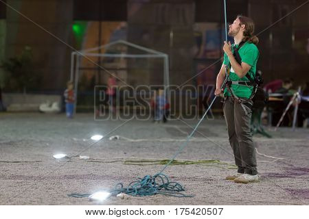 Belaying Referee holding Rope in night spot light at National Climbing Championship, Dnipro, Ukraine, May 21, 2016
