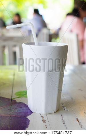 white plastic tall cup with water and straw
