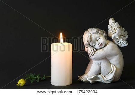 White candle an angel and flower on dark background