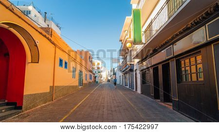 Glowing warm tones from indirect afternoon sun.  Man walks down the road in the streets of St Antoni de Portmany, Ibiza, Balearic Islands, Spain.