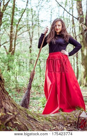 female witch standing with wooden broom in the spring forest