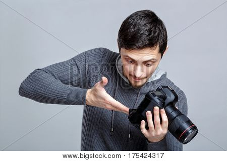 young photographer in shirt sets up the camera. guy learns to photograph on grey background