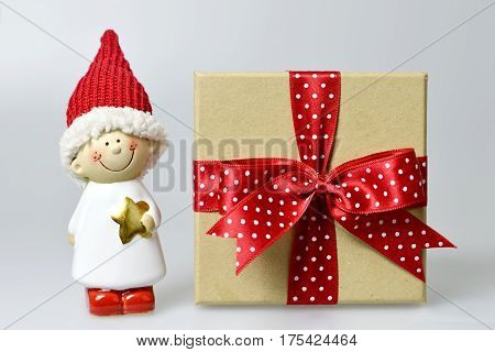 Christmas gift and Santa's helper on light background