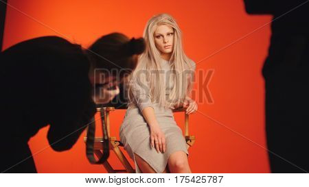 Handsome young woman in cocktail dress posing for photographer - fashion backstage, red background