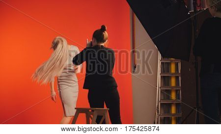 Fashion back stage - blonde model posing for photographer - flowing hair, red background