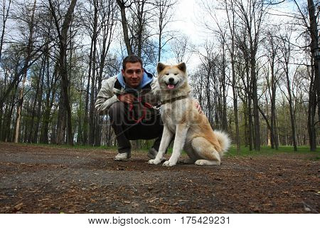 Akita inu female and young man posing in public park