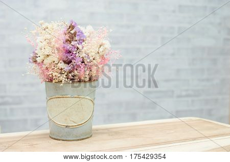 flower in retro vintage vase on wooden table with wall background, retro vintage concept with copy space for text.