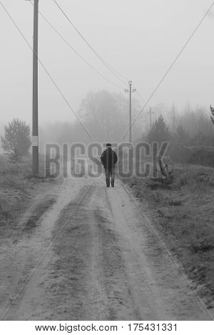 lonely figure of man walk on the country road in mist spring morning ( philosophy about choice road in life)