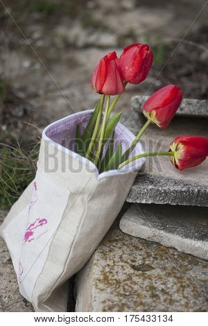spring festive bouquet of tulips in a makeshift packaging with embroidery