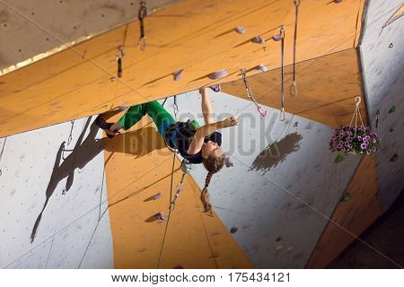 Female Climber trying to reach a hold on Climbing Wall. National Climbing Championship, Lead climbing Finals, Dnipro, Ukraine, May 21, 2016
