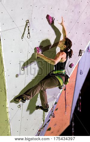 Female Athlete taking Hold on Climbing Wall at Night with spot light Illumination and sharp Shadow Silhouette
