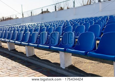 several rows of blue chairs on the stadium empty