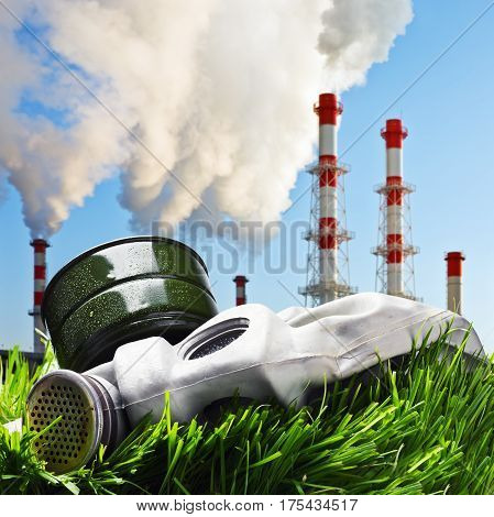 old gas mask on a green grass on a background of smoking chimneys polluting the planet