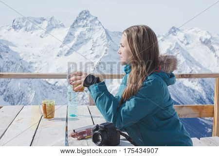 A Girl With Pleasure Drinks Tea In A Village Cafe In The Open Air.