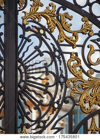 Detail of an ornate gilded gate outside Tsarskoe Selo Palace in Pushkin near Saint Petersburg Russia.