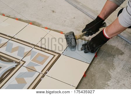 Specialist For Laying Tiles Aligns The Tiles With A Carpenter's Hammer In The Living Room Of A City