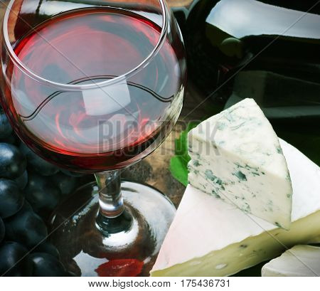 glass of red wine and grapes are ripe. Focus on a glass of wine
