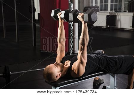 Man Lying On Bench Press While Exercising With Dumbbell