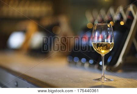 Wine bottles on a wooden shelf. Wine bar. Close up on glass of white wine
