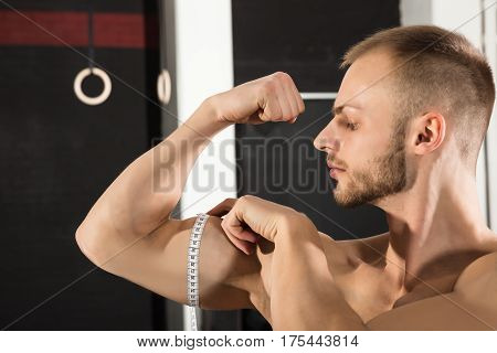 Young Athlete Man Measuring Arm With Tape Measure In The Gym