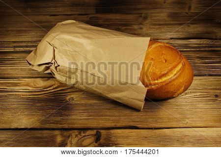 Bread Packed In Paper On Wooden Table