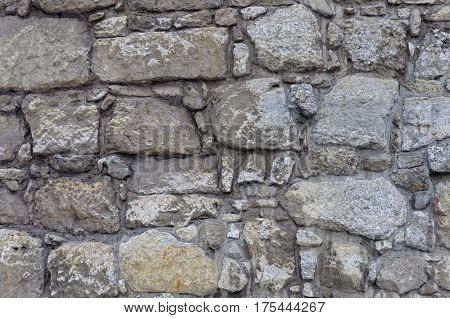Texture of gray stone wall of ancient tower