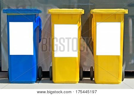 Three colorful plastic trash cans on street