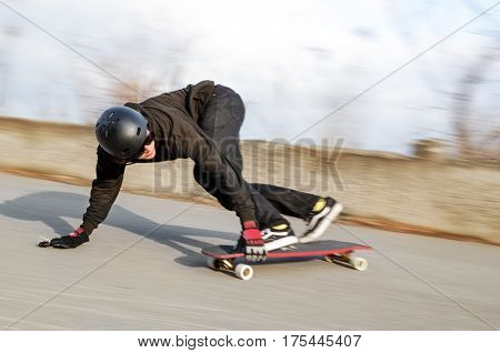 Young man in helmet is going to slide, slide with sparks on a longboard on the asphalt at sunset