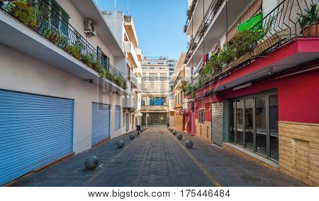 Vacant & shaded, empty alleyway on otherwise bright sunlit day in Sant Antoni De Portmany.  Ibiza in quiet off-season in the afternoon.