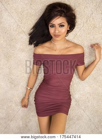 Beautiful woman wearing burgundy cocktail dress lying on rug looking up
