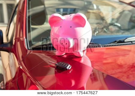 Close-up Of A Piggybank With Car Key On New Red Car
