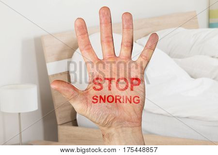 Close-up Of Stop Snoring Written On Hand In Bedroom At Home