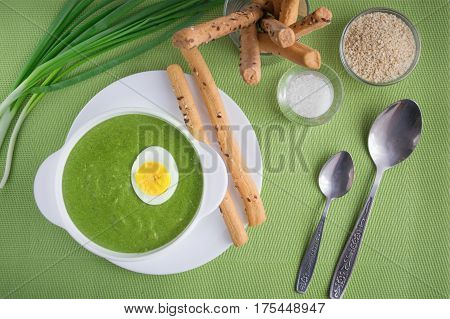 Spinach cream soup with egg and breadsticks