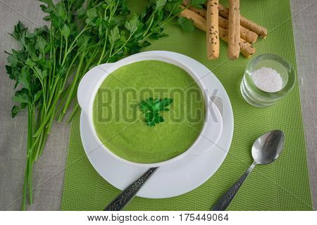 Spinach cream soup with parsley and breadsticks