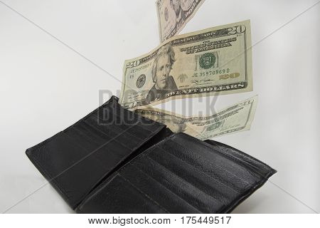 United States of America currency is flying out of a wallet..