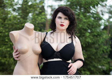 Young beautiful busty curvy plus size model with big breast in black bra holding mannequin xxl woman professional makeup and hairstyle