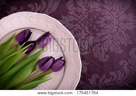 Fresh violet tulips on plate, violet table-cloth