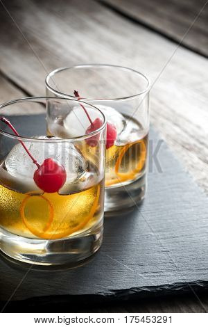 Old fashioned cocktails with maraschino cherries on the board