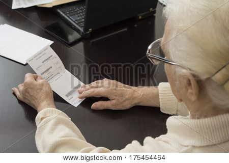 Old woman in doctor's office. The old woman holds in her hands a prescription and reads